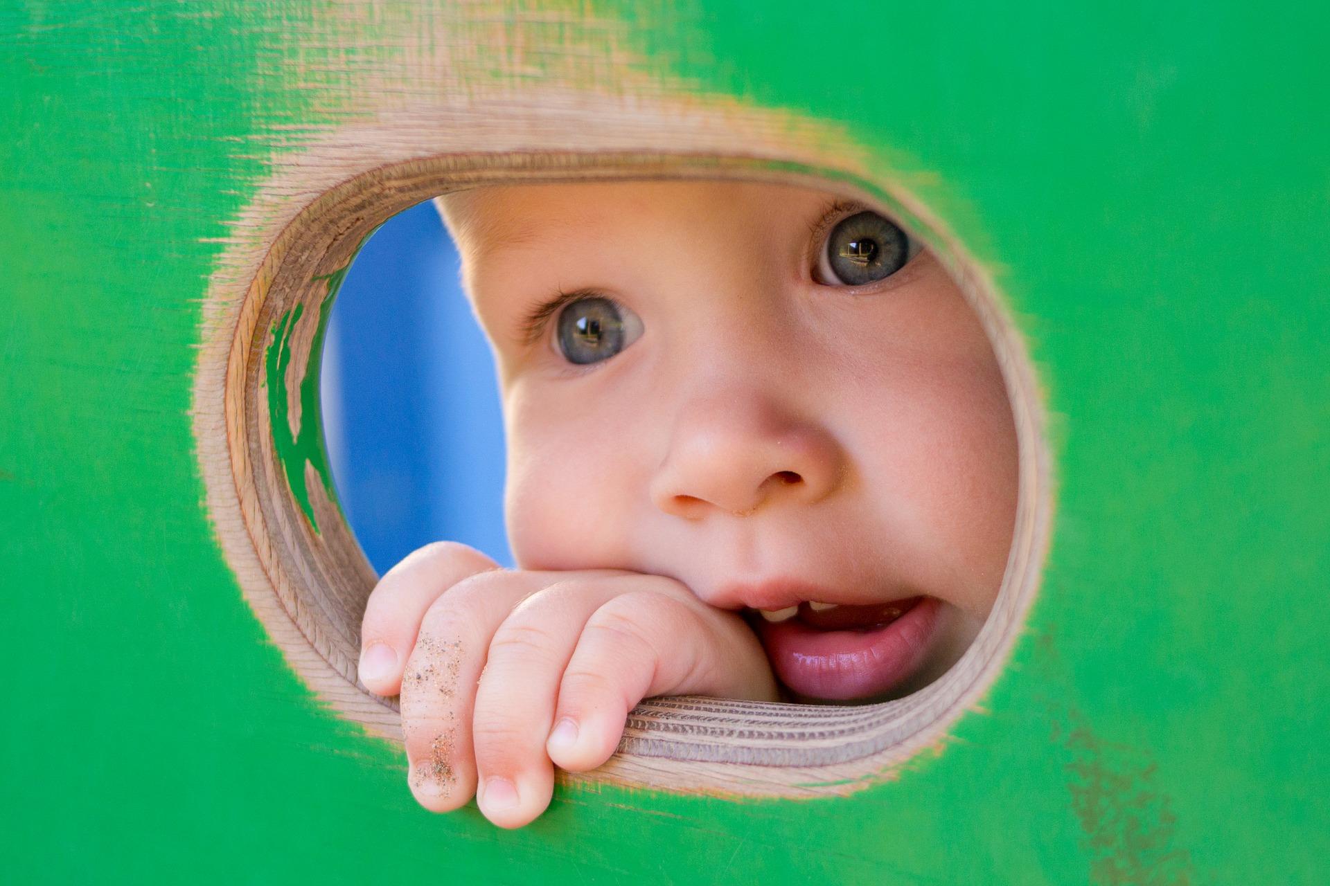 dziecko wygląda przez dziurę
